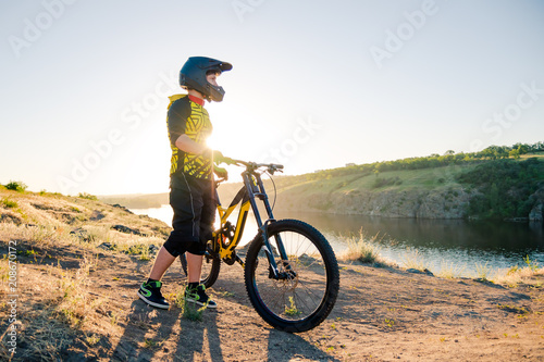 Fotobehang Fiets Cyclist Preparing for Riding the Mountain Bike on the Summer Rocky Trail at the Evening. Extreme Sport and Cycling.