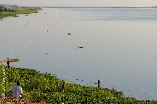 Fotografie, Obraz  Villager fishing off riverbank in Malawi, Africa