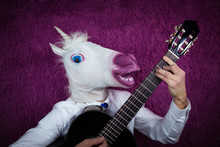 Freaky Young Man In Comical Mask Playing The Guitar On The Purple Background. Portrait Of Unusual Guy In Shirt And Tie With Musical Instrument. Musical Performance.