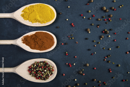 Fotobehang Kruiderij Different spices in wooden spoons and pepper scattered on concrete background
