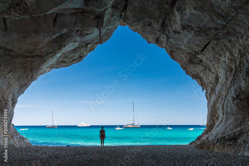 Woman inside a cave at Cala Luna beach Wallpaper Mural