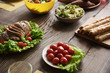 Close up of baked meat lying on lettuce together with white plate of cherry tomatoes. Bread and salads in bowls are nearby