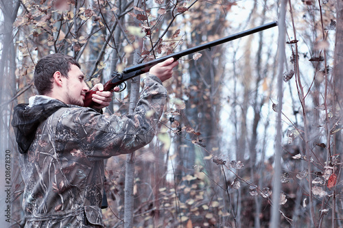 Fotobehang Jacht A man in camouflage and with a hunting rifle in a forest on a sp