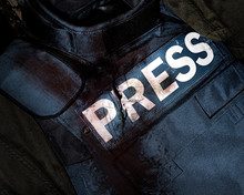 Photo Of A Press Journalist Armor War Protective Vest In Blood Splatter Depicting Mass Media War Victims.