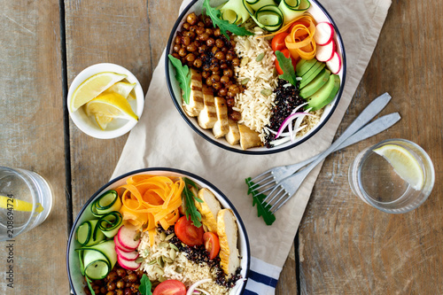Foto op Plexiglas Boeddha Top view two buddha bowl lemon water Clean balanced healthy food concept Chicken grilled steak rice spicy chickpeas black white quinoa avocado carrot zucchini radish tomatoes wooden table
