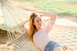 Young blonde female person lying in white wicker hammock on sand, wearing jeans shorts and shirt. Concept of summer vacations and resting on beach.
