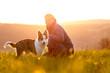 Frau und kleiner Hund oder Welpe auf einer Wiese bei Sonnenaufgang, Gegenlicht