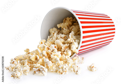 Popcorn in striped bucket isolated on a white background.
