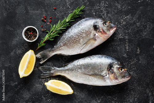 In de dag Vis Fresh dorado or sea bass fish on slate background with cooking ingredients, lemon rosemary and spices. Top view