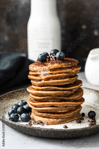 Oat pancakes with blueberry, chocolate and honey. Healthy pancakes. Healthy breakfast or snack concept. Closeup view stack of pancakes