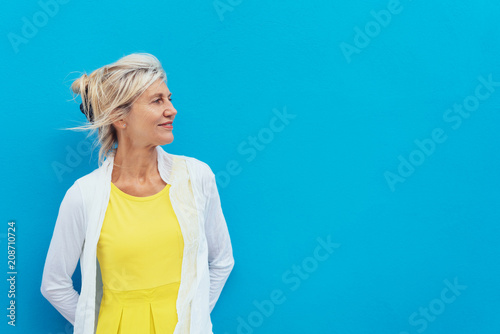 Fotografia  Relaxed confident blond woman against a blue wall