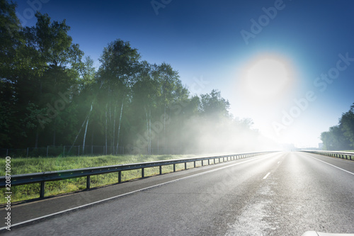 Printed kitchen splashbacks Khaki Asphalt road with metal safety barrier near the forest with thick fog over the sun.