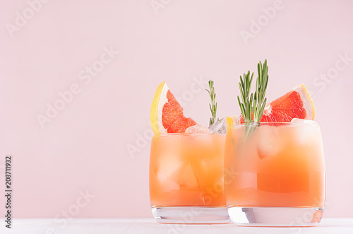 Staande foto Cocktail Cold lemonade of fresh grapefruit juice, alcohol and ice cubes decorated slice citrus and twig rosemary on fashion pastel pink background.