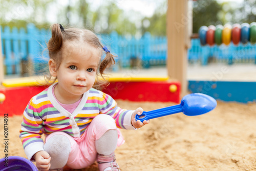 Fotografie, Obraz  a little girl with two tails is dressed in a striped colorful jacket is playing