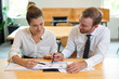 Business man and woman discussing diagram in office. Colleagues pointing at chart on paper with blurred office interior in background. Business analysis concept. Front view.