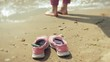 Summer shoes on the beach. in the background of a girl walking and dancing on the sand