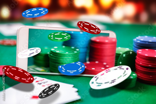 Fotografija  Smartphone with fly gambling chip, online poker table application