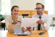 Smiling business coworkers working and discussing document. Business woman and man using tablet computer and looking at camera with blurred office interior in background. Coworkers concept.