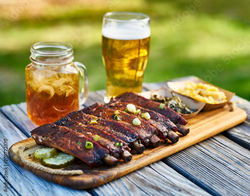 Aluminium Prints Grill / Barbecue st louis style bbq ribs with collard greens and mac & cheese outside on picnic table during sunny summer day