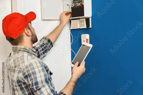 Photo Young electrician installing alarm system