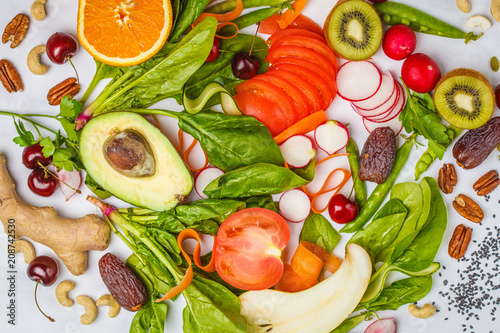 Raw fresh vegetables, fruits, berries, nuts on a white background. Healthy food background, top view. Go vegan concept.
