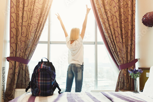 Woman standing near the window in hotel room Wallpaper Mural