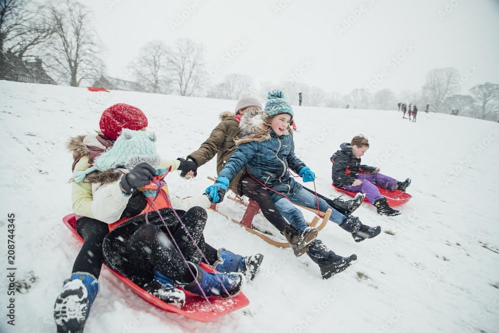 Fototapeta Children Having a Sledding Race