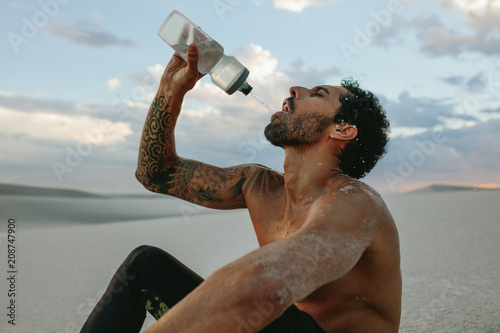 Fotografía  Athlete getting hydrated after workout in desert