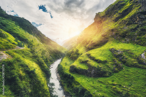 View with amazing mountains covered green grass, river, meadows and forest, blue sky with clouds, sun in autumn in Nepal at sunset. Mountain valley at bright sunny evening. Travel in Himalayas. Nature