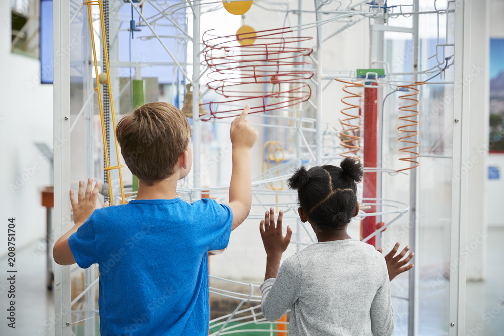 Fototapety, obrazy: Two kids looking at a science exhibit,  back view