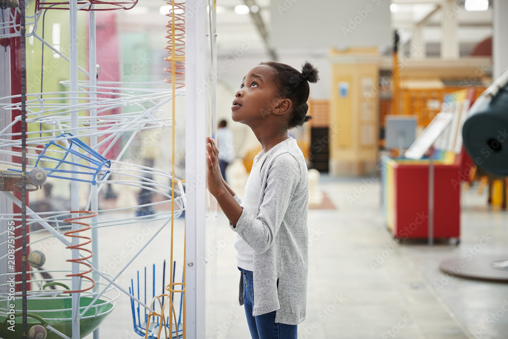 Fototapety, obrazy: Young black girl looking at a science exhibit, close up