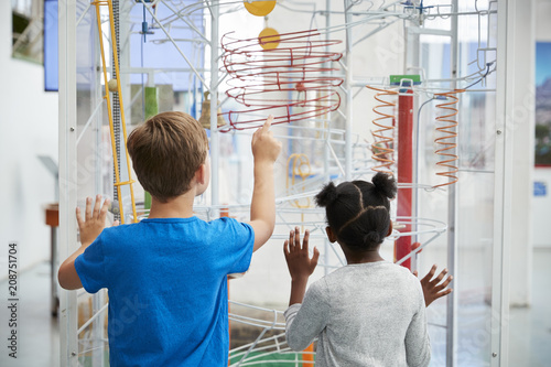 Obraz Two kids looking at a science exhibit,  back view - fototapety do salonu