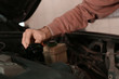 Auto mechanic repairing car in service center, closeup