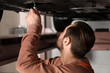 Young auto mechanic repairing car in service center