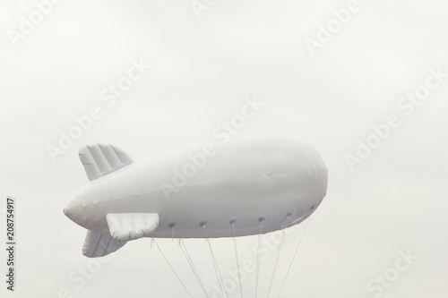 White inflatable dirigible with a place for a logo on a background of a gray sky with clouds. Copy space
