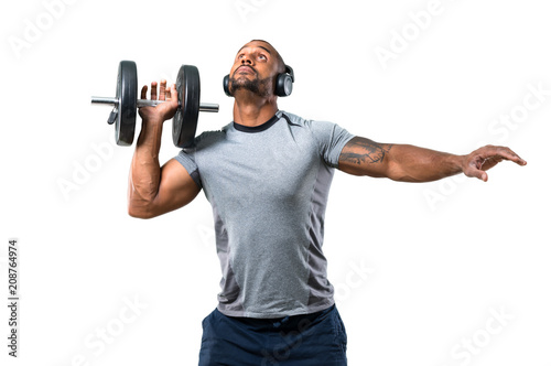 Strong handsome sport man making weightlifting and listening music on isolated white background