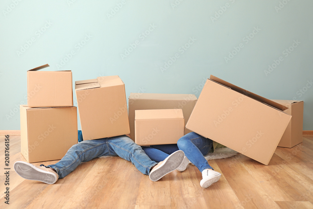Fototapety, obrazy: Young couple buried under heap of boxes indoors. Moving into new house