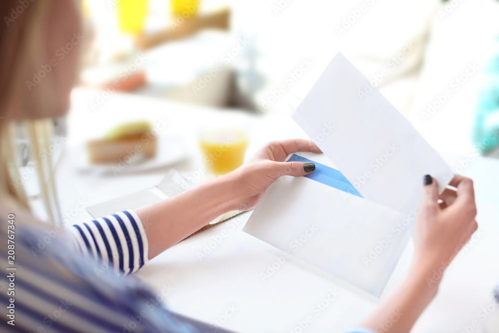 Fototapeta Young woman putting letter into envelope at table in cafe. Mail delivery