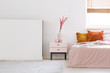 Real photo of a pink, feminine bedroom interior with orange cushions on bed and flowers on a nightstand next to an empty wall