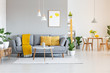 Leinwanddruck Bild - Orange blanket on grey sofa in modern apartment interior with poster and wooden table. Real photo