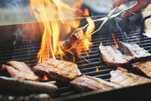 Close-up Of Man Preparing Meat On Grill