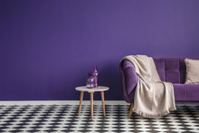 Dark Purple Sofa With A Blanket Beside A Small Table With Bottles Standing On Black And White Checkerboard Floor In A Minimalistic Living Room Interior. Copy Space. Real Photo