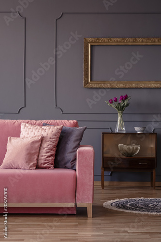 Fototapety, obrazy: Cropped photo of a sofa, pillows, cabinet with flowers and empty golden frame on a grey wall