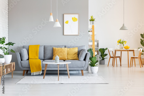 Photo Orange blanket on grey sofa in modern apartment interior with poster and wooden table