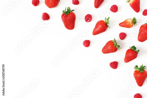 Summer healthy fruit composition with fresh red strawberries and raspberries isolated on white table background. Food pattern. Empty space. Flat lay, top view. Styled stock photo.