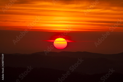 Papiers peints Orange eclat Natural Sunset Sunrise Scene Over highland or mountains. Bright Dramatic Sky And Dark Ground. Countryside Landscape Under Scenic Colorful Sky At Daybreak Dawn. Sun Over Skyline, Horizon. Warm Colors.