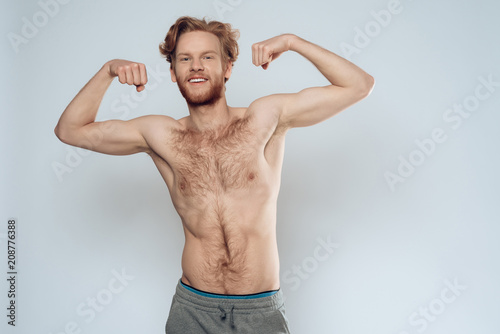 Photographie Bare redhead man shows muscles.
