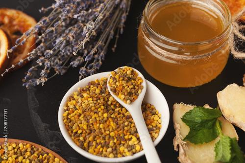 Various types of honey on wooden platter, closeup Canvas Print
