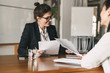 Leinwanddruck Bild - Photo of successful woman holding resume and negotiating with female candidate during corporate meeting or job interview - business, career and placement concept