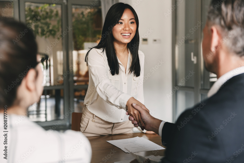 Fototapeta Business, career and placement concept - image from back of two employers sitting in office and shaking hand of young asian woman, after successful negotiations or interview